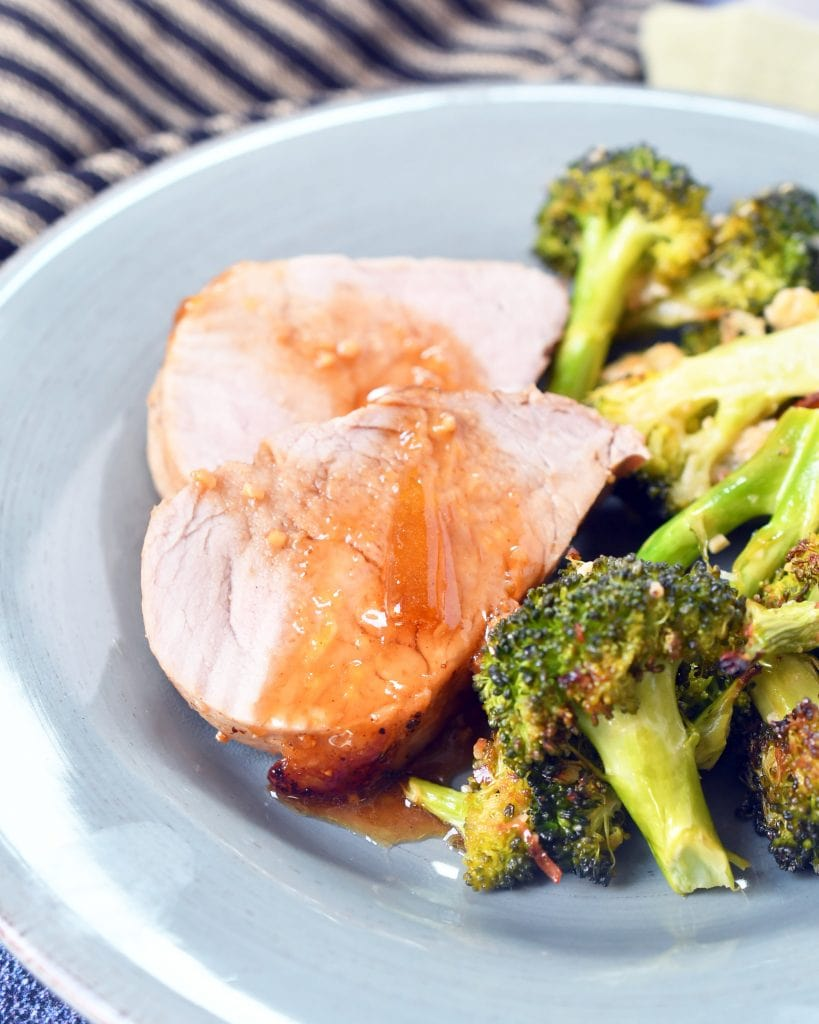 2 slices of pork tenderloin drizzled with peach honey sauce next to roasted Parmesan broccoli on a blue plate