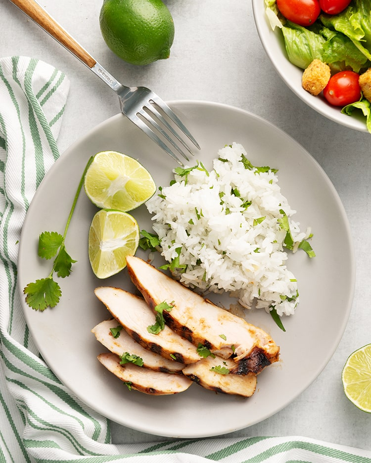Sliced honey lime chicken on a plate with cilantro rice and limes