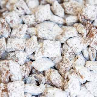 A close up on muddy buddies, which shows the chex cereal coated in chocolate, and powdered sugar.