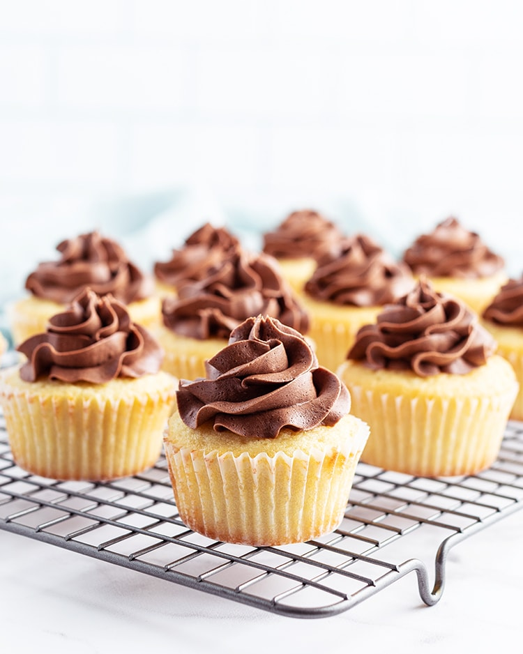 Yellow cupcakes with chocolate frosting on a cooling rack.