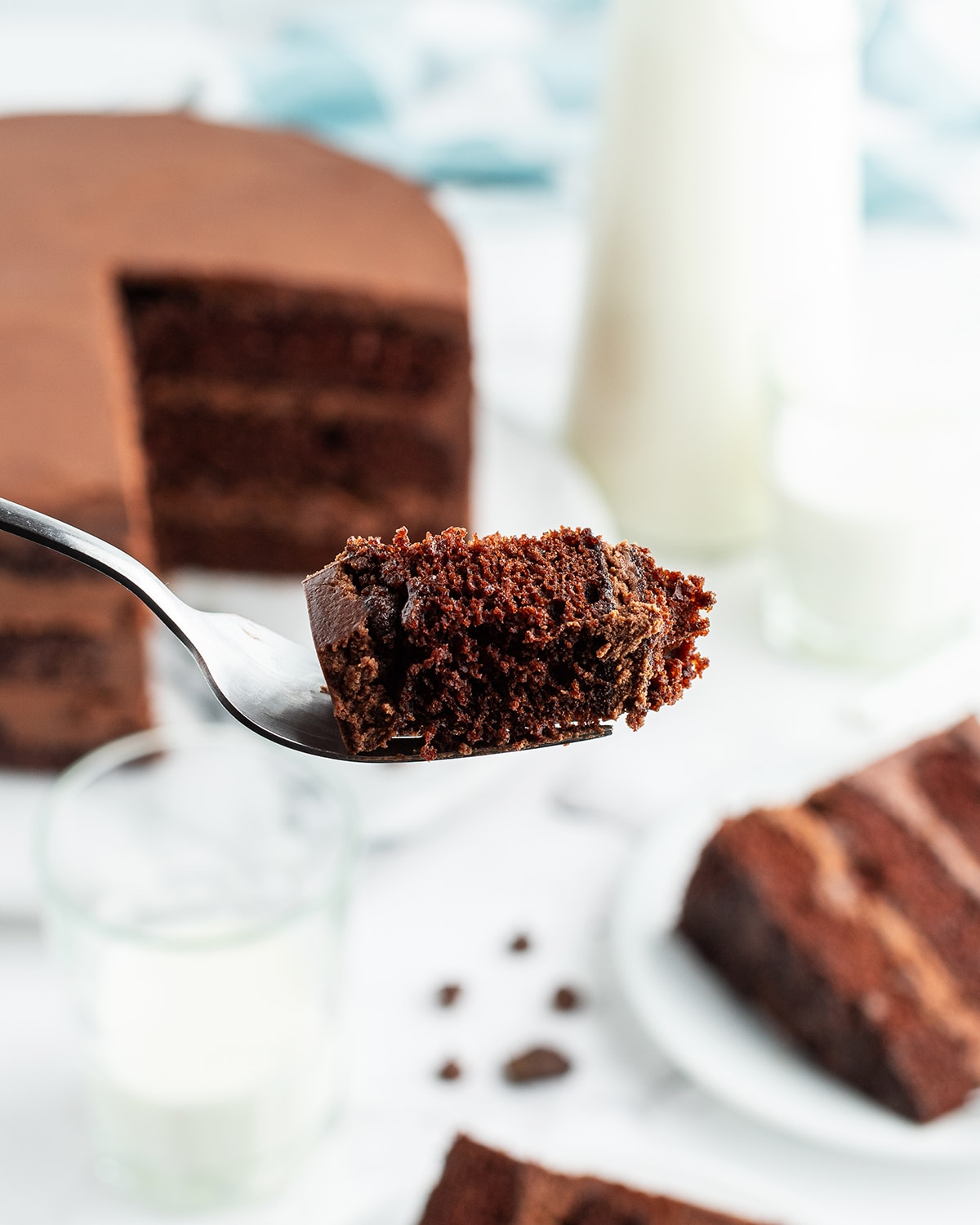 A bite of chocolate cake on a fork with the slice in the background.