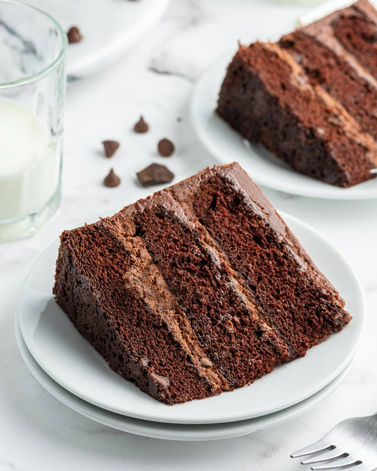 A slice of chocolate cake with three layers and chocolate frosting on a white plate. There is another slice in the back.