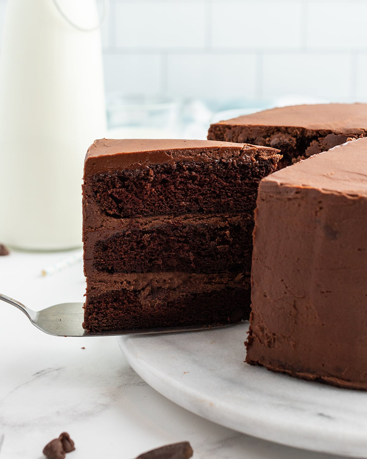 A chocolate cake slice being pulled out of a cake on a cake server.