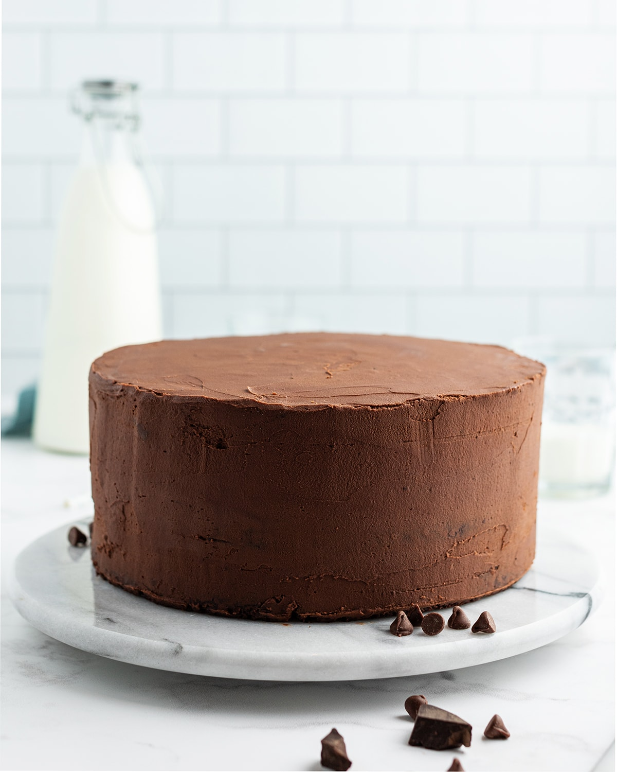 A chocolate cake, plainly frosted with smooth chocolate frosting on a white marble cake turner.