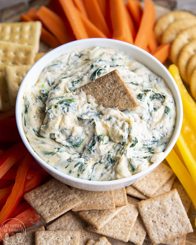A bowl of a cheesy spinach dip, surrounded by crackers, and carrots, with a wheat thin in the dip.