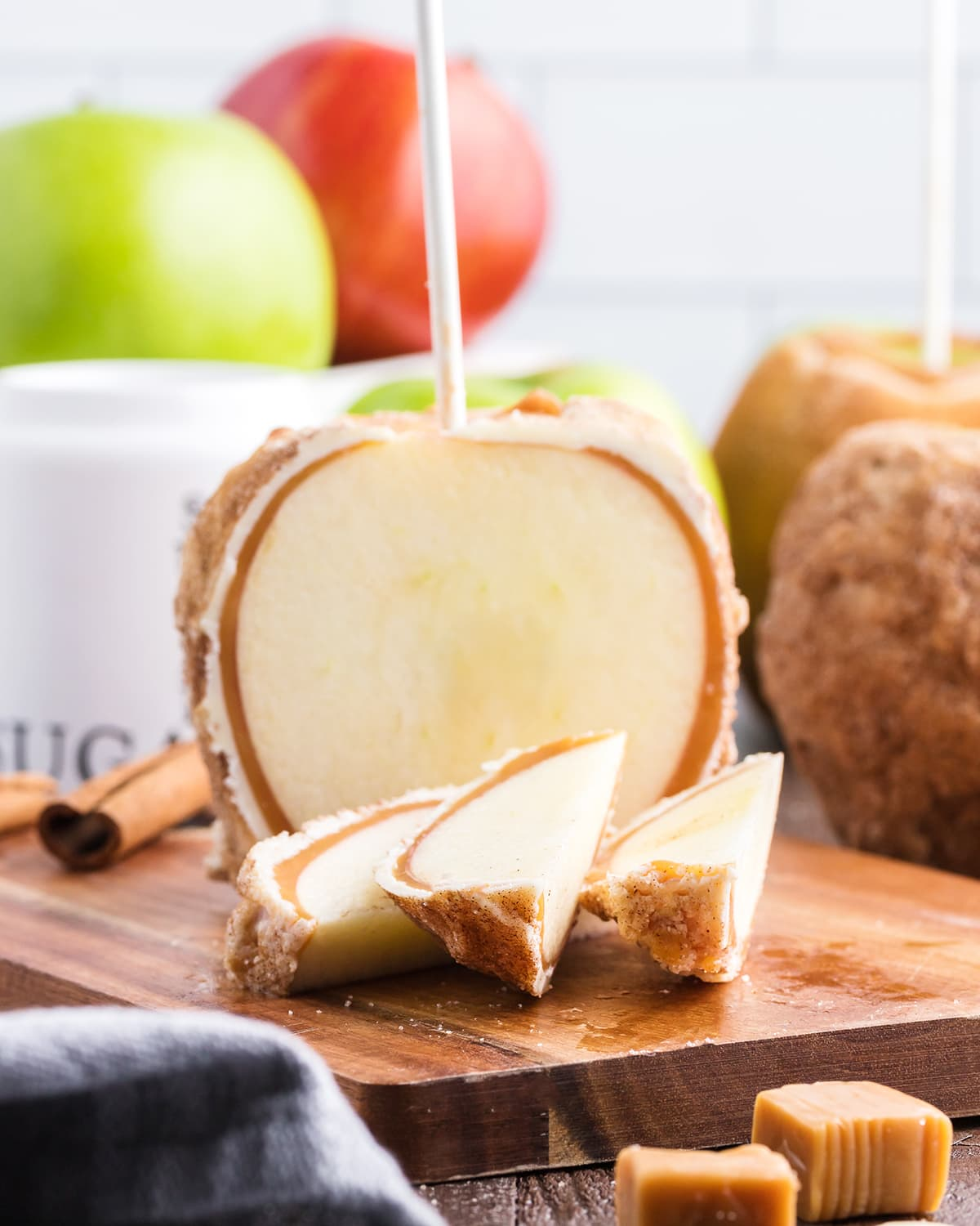 A cinnamon caramel apple cut up with three slices laying in front of it.