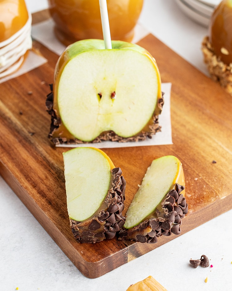Slices of a caramel apple with chocolate chips on it.