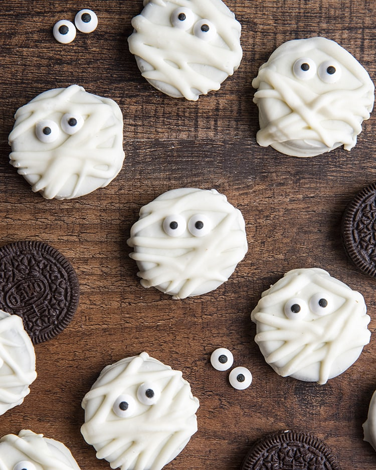 Mummy Oreos on a wooden board, they are white chocolate dipped Oreos decorated with candy eyes and drizzled to look like mummies.