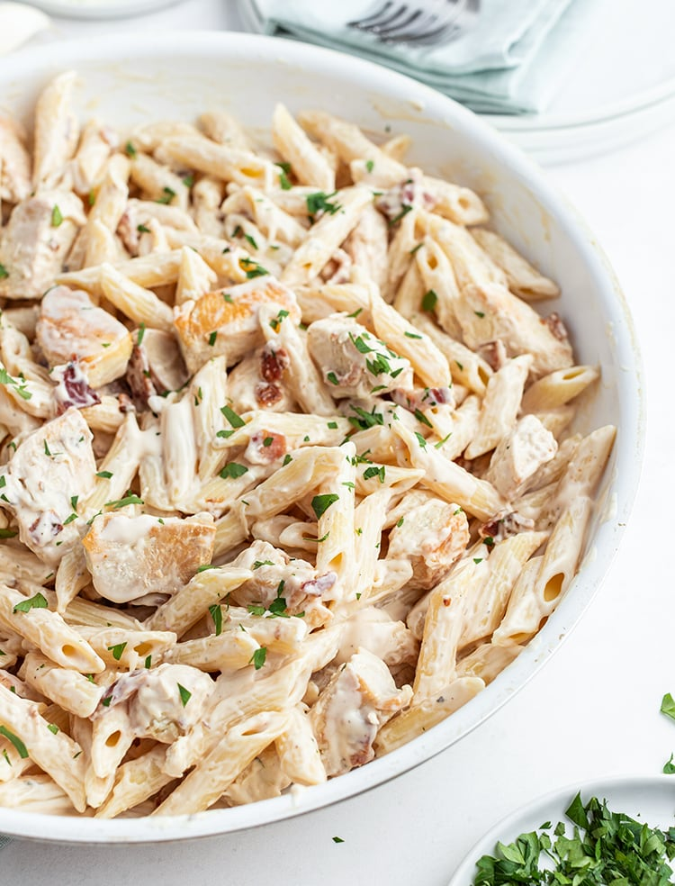 A Pasta dish in a pan with penne noodles and chicken in a white sauce. Topped with parsley.