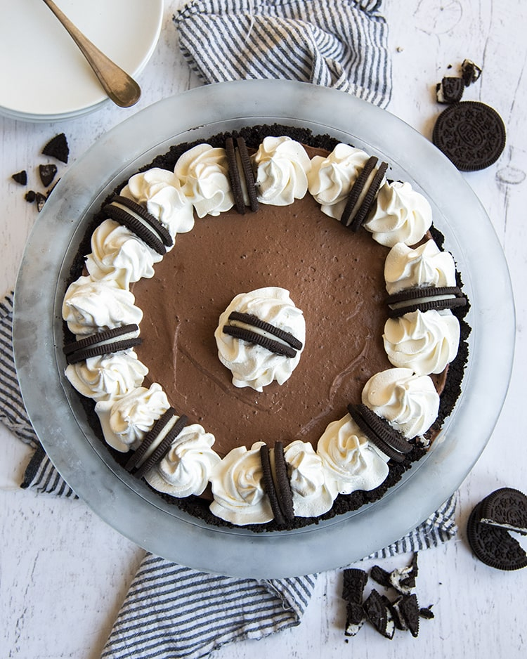 A chocolate cream pie in a pie pan topped with whipped cream and Oreos.