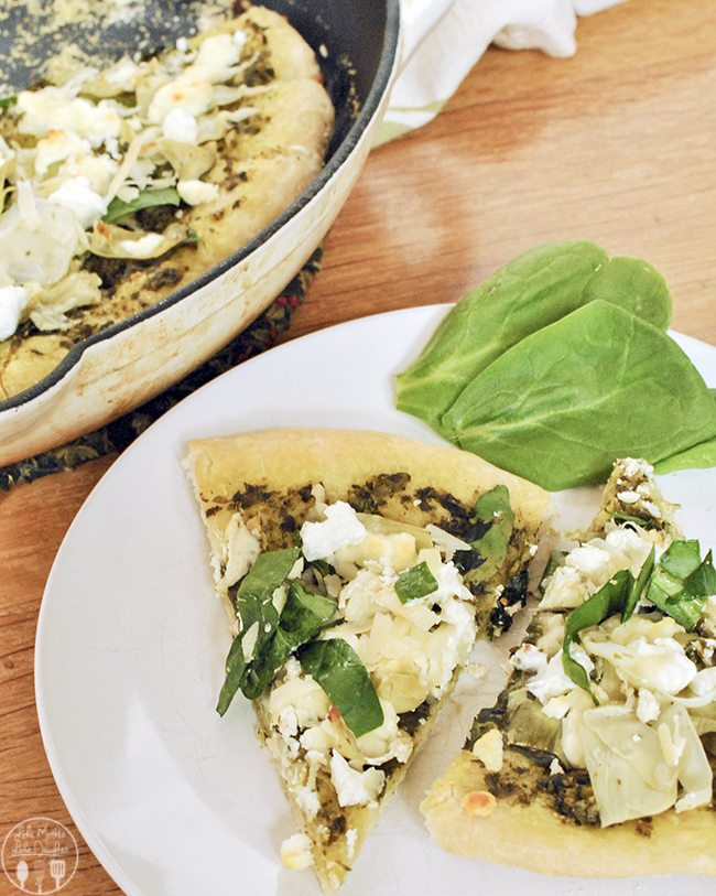 Spinach Artichoke Pizza - this delicious pizza has a basil pesto base, healthy spring vegetables of spinach and artichokes, creamy goat cheese, and a dash of Parmesan for a yummy flavorful pizza.