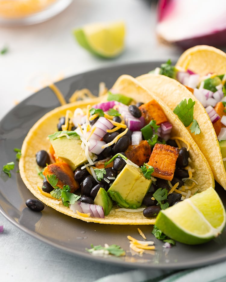 Sweet Potato and Black Bean Tacos topped with avocado, cheese, and lime juice.