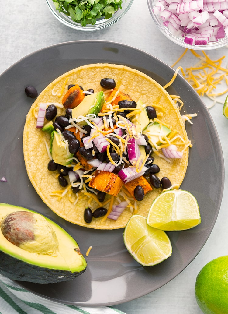 A sweet potato and black bean taco on a plate with an avocado and lime on the side.
