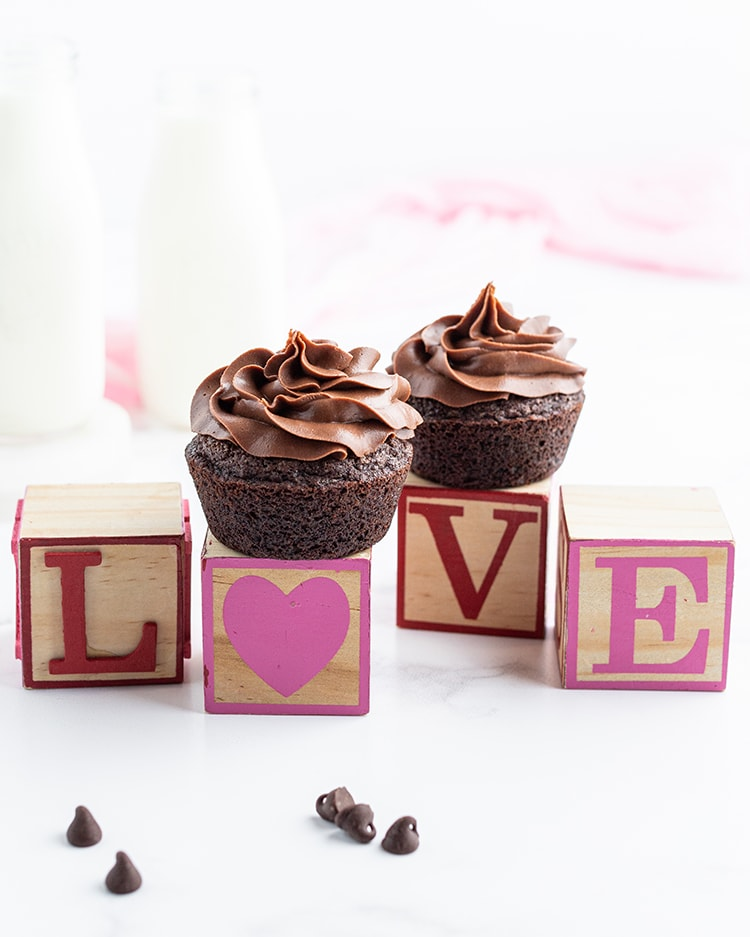 Blocks spelling out the word love in pink and red paint, the o is a heart. There is a chocolate cupcake on top of the heart block and the v block.