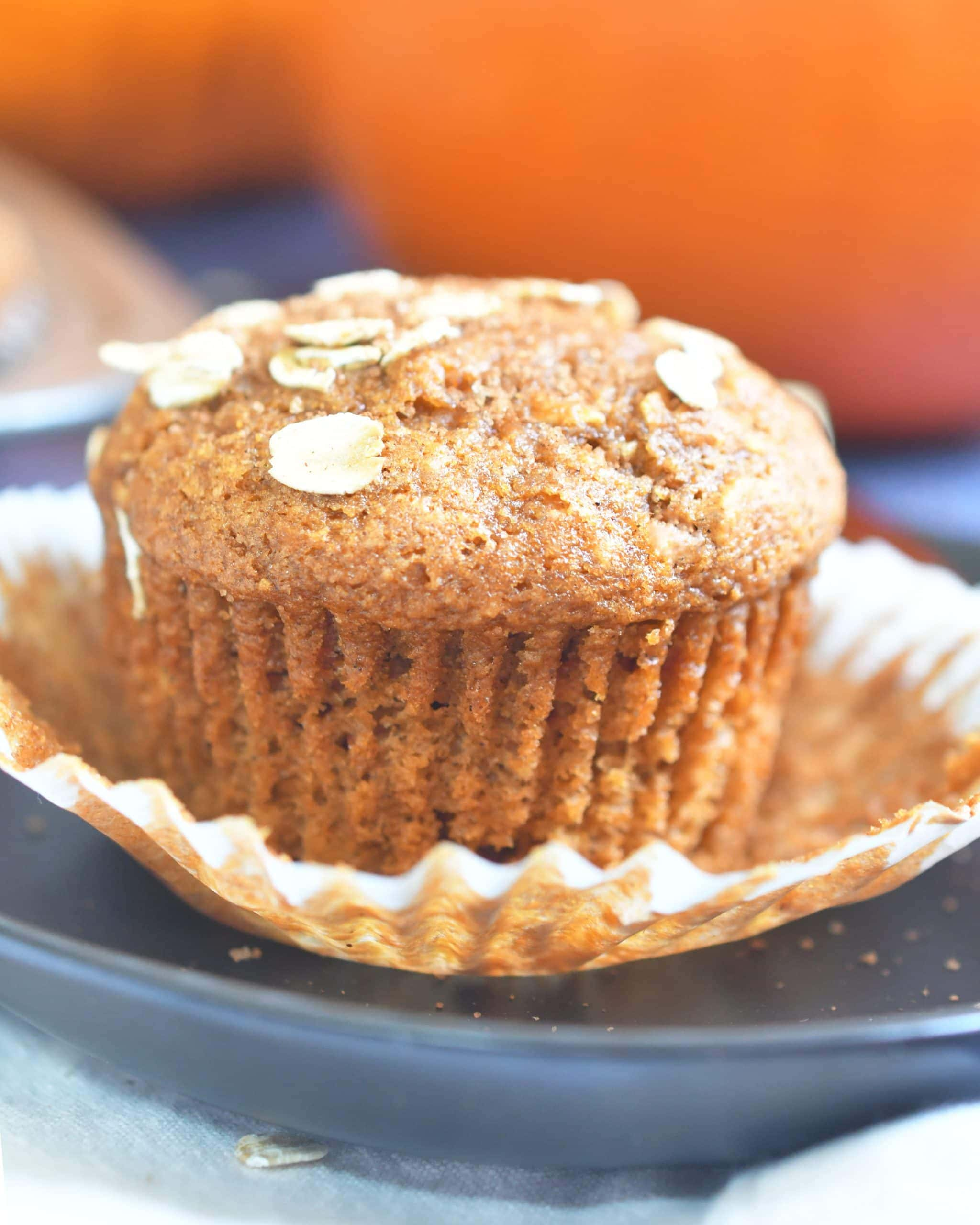 pumpkin oat muffin on a paper liner on top of a brown plate with an orange pumpkin in the background