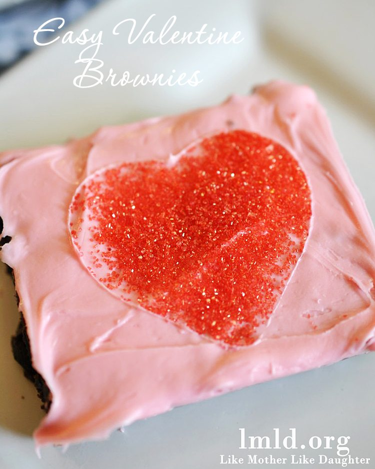 Valentine's Day Brownies are a fun brownie topped with pink frosting and a heart pattern made with sprinkles!