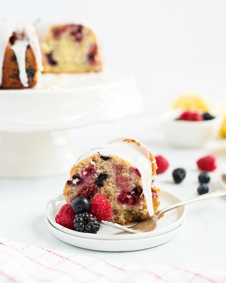 A slice of lemon berry bundt cake with lemon glaze on top on a white plate