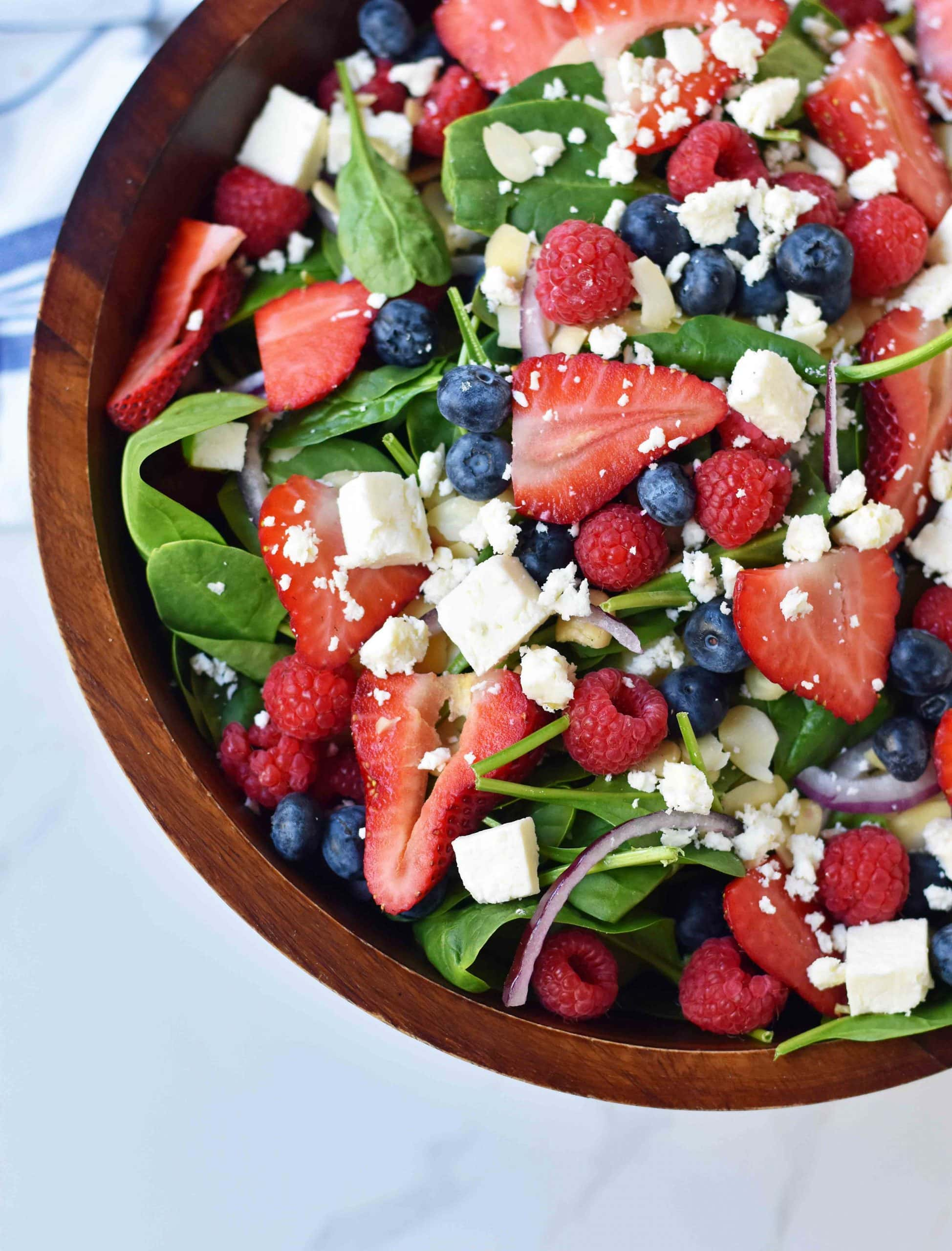 A salad in a wooden bowl full of spinach, fresh berries and feta cheese crumbles.