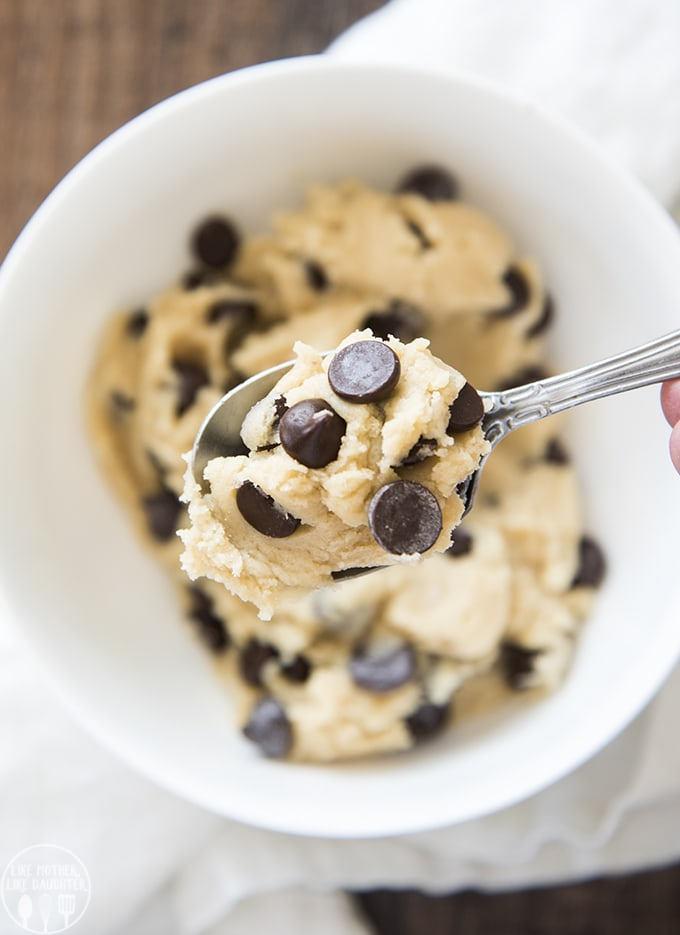 A spoonful of cookie dough topped with chocolate chips, being held above a bowl of cookie dough.