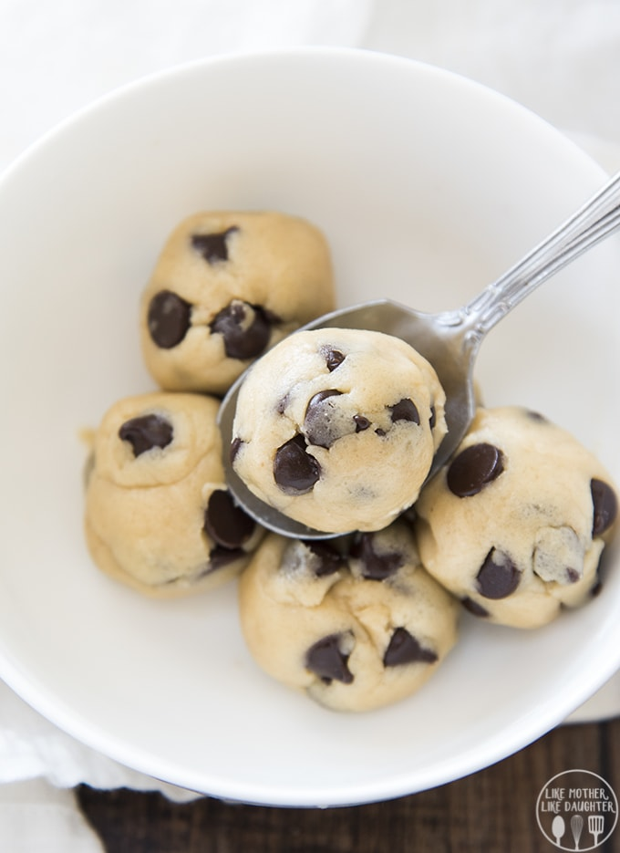 A bowl of 6 small balls of cookie dough. There are lots of chocolate chips peaking through the cookie dough. One of the balls is on a spoon.