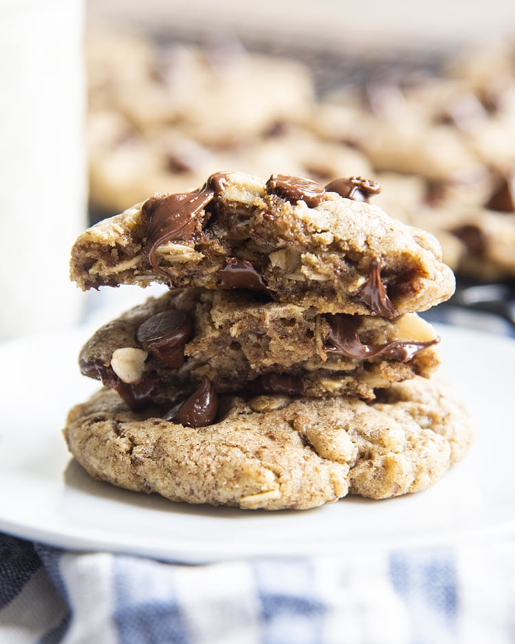 A stack of chocolate chip cookies, the top cookie is broken in half to show the melted chocolate chips and oats in the middle.
