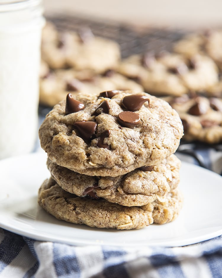 A stack of three cookies with chocolate chips on them on a small plate. The cookies look slightly darker in color than normal from having flax in them.