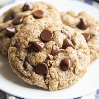 A close up of three oatmeal flax chocolaet chip cookies on a small plate. The cookie in front is topped with 6 chocolate chips.