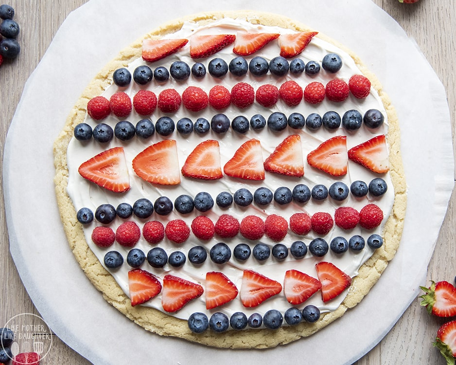 Red White and Blue Fruit Pizza with blueberries, strawberries, and raspberries on top.