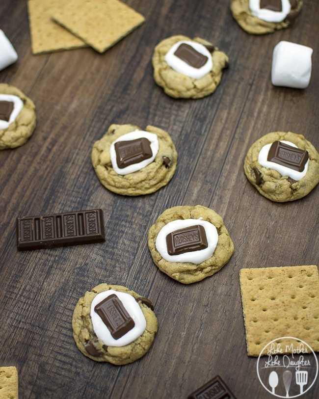 S'mores Cookies - These delicious s'mores cookies have a simple chocolate chip cookie base mixed with a graham cracker crumble and are topped with a gooey marshmallow and hershey's chocolate for the great taste of s'mores in a delicious cookie!