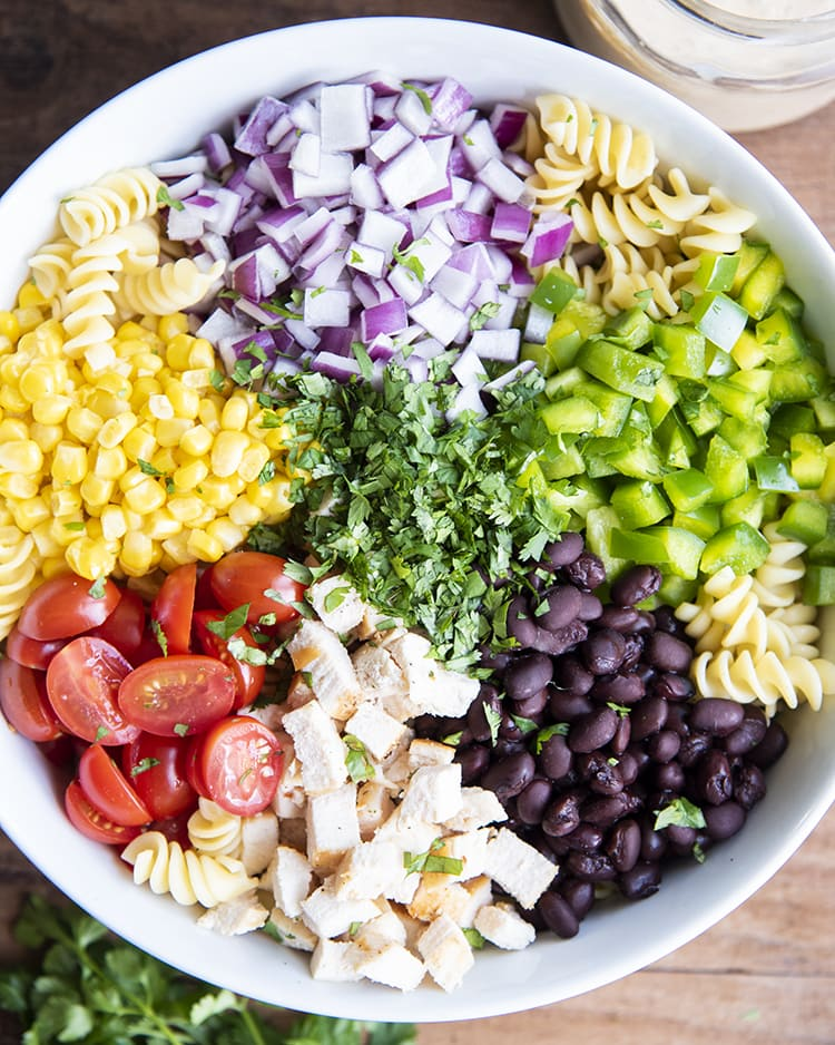 A bowl of noodles, red onion, bell peppers, black beans, chicken, tomatoes, corn, and cilantro