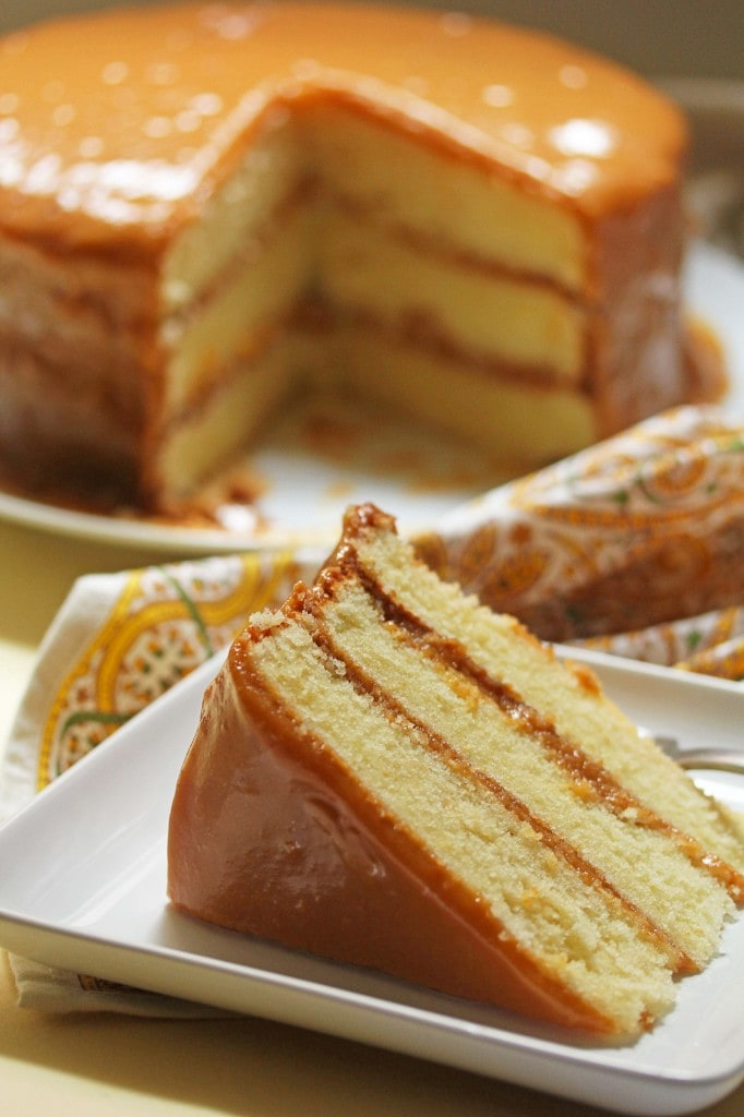 A slice of caramel cake with caramel topping