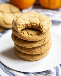 A stack of pumpkin snickerdoodle cookies. The top cookie has a bite taken out of it.