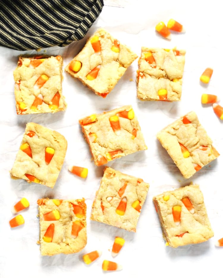 Candy corn peanut butter bars cut into pieces and laying out randomly with pieces of candy corn between them.