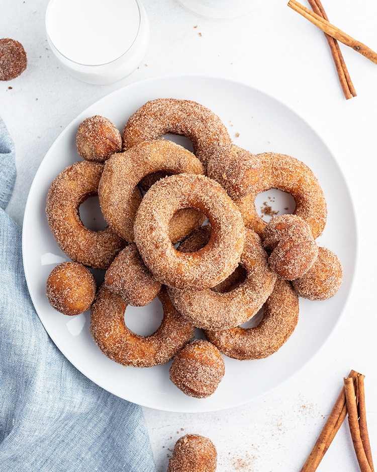 A plate full of cinnamon sugar biscuit donuts, with some donut holes on the plate too. There are cinnamon sticks and a cup of milk on the side of the plate.