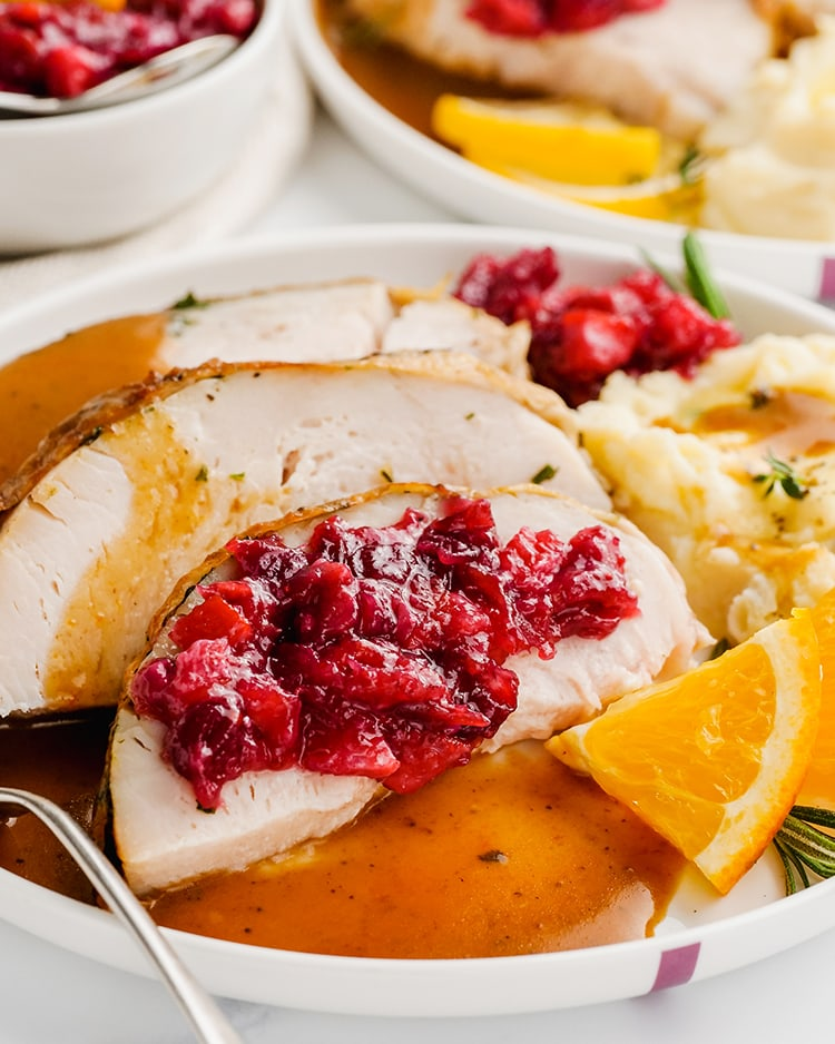 A plate of turkey topped with cranberry orange sauce and mashed potatoes.