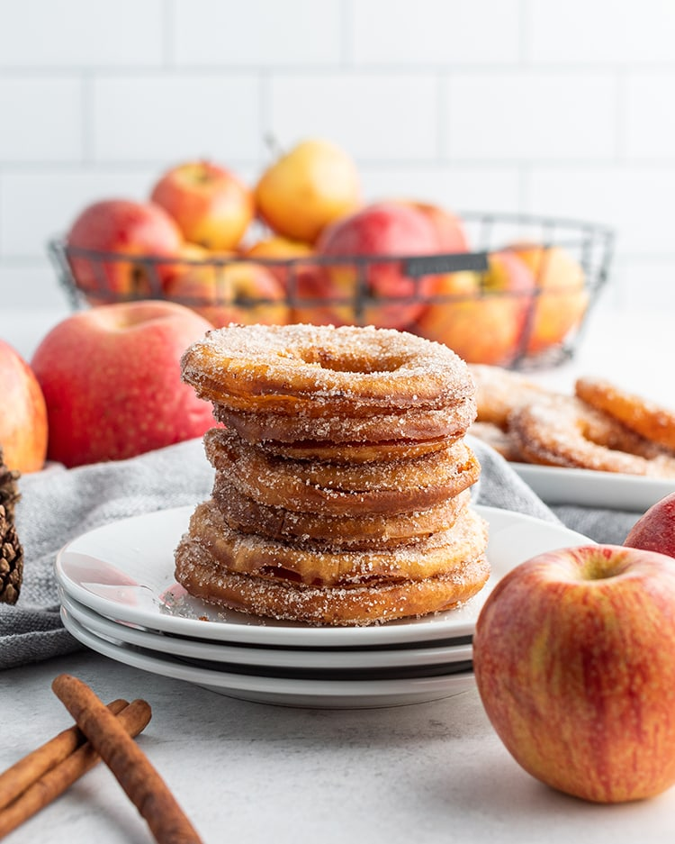 A stack of apple rings coated in cinnamon sugar and set on a plate with a basket of apples in the back