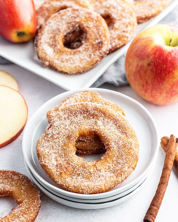 Two deep fried apple rings on a plate.