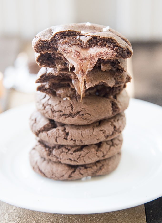 A stack of 7 rolo cookies. The top 2 cookies are broken in half to show the gooey caramel from the rolo, that is coming out of the cookie.
