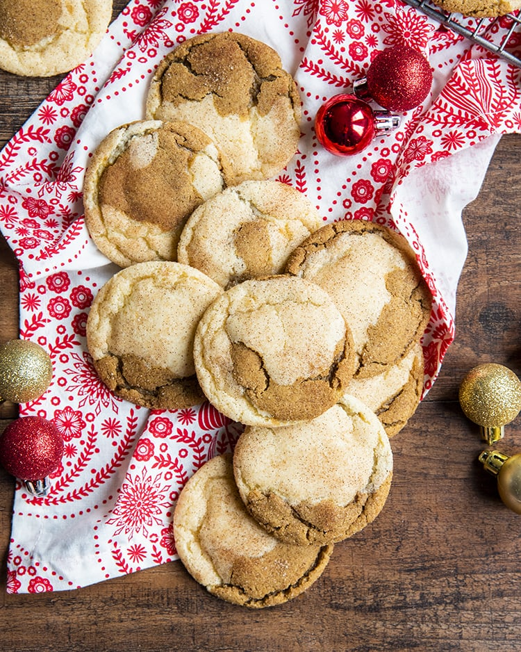 A pile of half snickerdoodle half ginger molasses cookies on a red and white cloth.