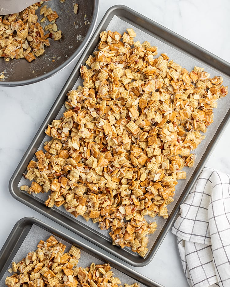 Gooey coconut chex mix on a cookie sheet. It has rice chex, golden grahams, almonds, and coconut.