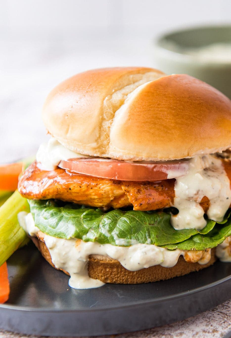 A chicken sandwich with a creamy white sauce, lettuce, a chicken breast with buffalo sauce, and a slice of tomato, on a bun.
