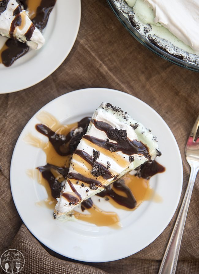 Mint Chocolate Chip Ice Cream Pie - This delicious ice cream pie has a homemade chocolatey oreo crust, filled with a creamy mint chocolate chip ice cream, topped with whipped cream and drizzled with caramel and chocolate syrup! Its going to become your new favorite frozen dessert!