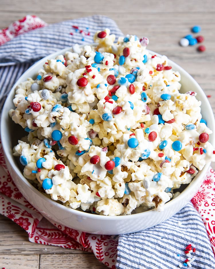 White Chocolate Popcorn with red white and blue m&ms and sprinkles in a white bowl