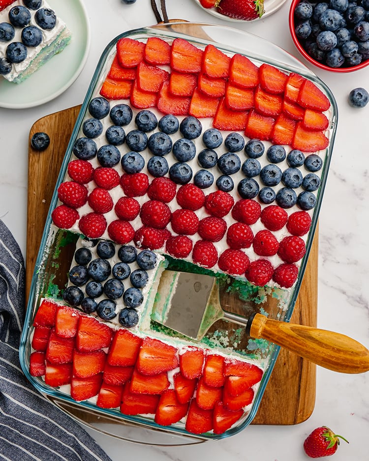 A cake in a pan with stripes of strawberries, blueberries and raspberries with a slice removed.