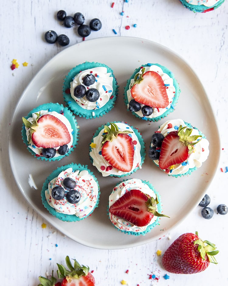 A plate of mini cheesecakes shot from above, showing their blue color topped with whipped cream, and fresh blueberries and strawberries.