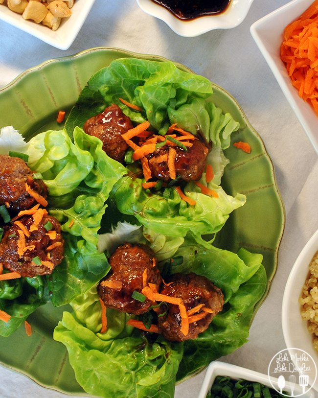 Six teriyaki meatballs on lettuce sprinkled with carrots and minced onions, on a green plate