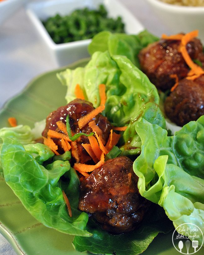 Four teriyaki meatballs on lettuce sprinkled with carrots and minced onions, on a green plate