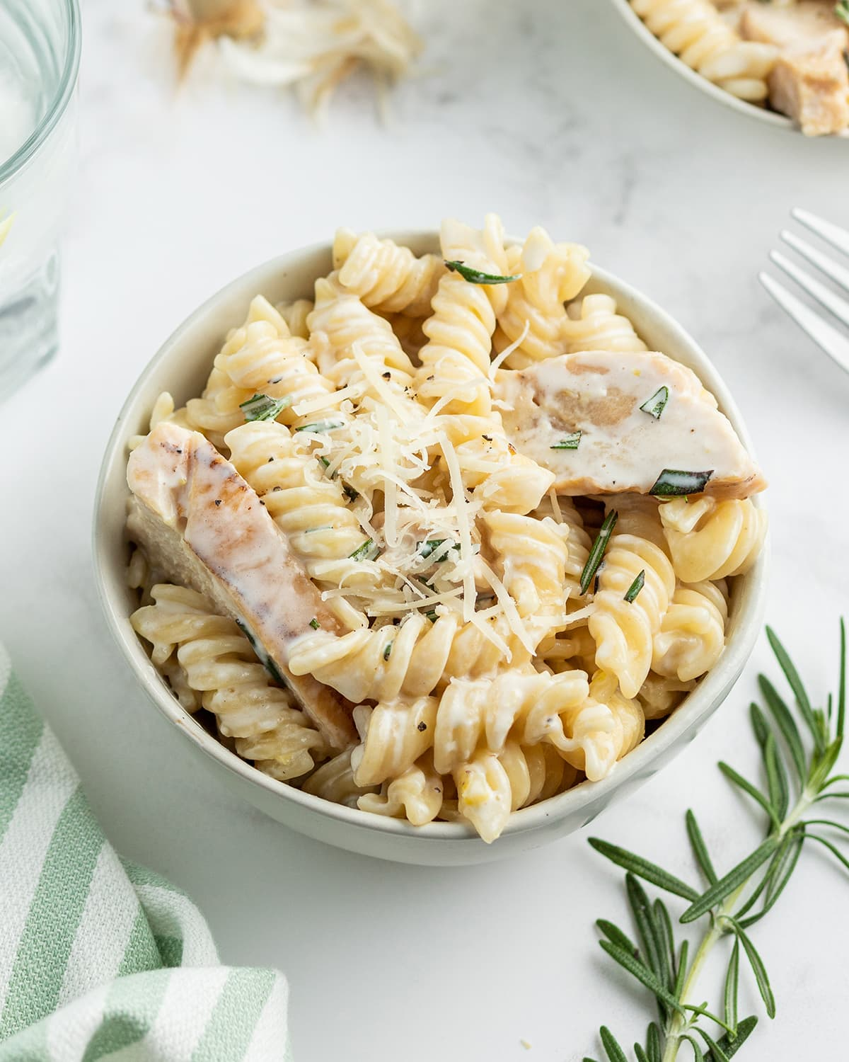 A bowl of lemon chicken pasta with a creamy white sauce, rotini pasta and chunks of grilled chicken, topped with shredded parmesan cheese.