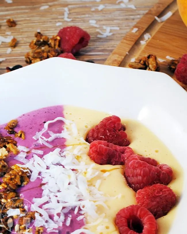 Peach Berry Smoothie Bowl - a breakfast of peaches, berries, yogurt, and juice blended together on topped with nuts, coconut and raspberries for a flavor bursting healthy breakfast you will want to eat everyday!