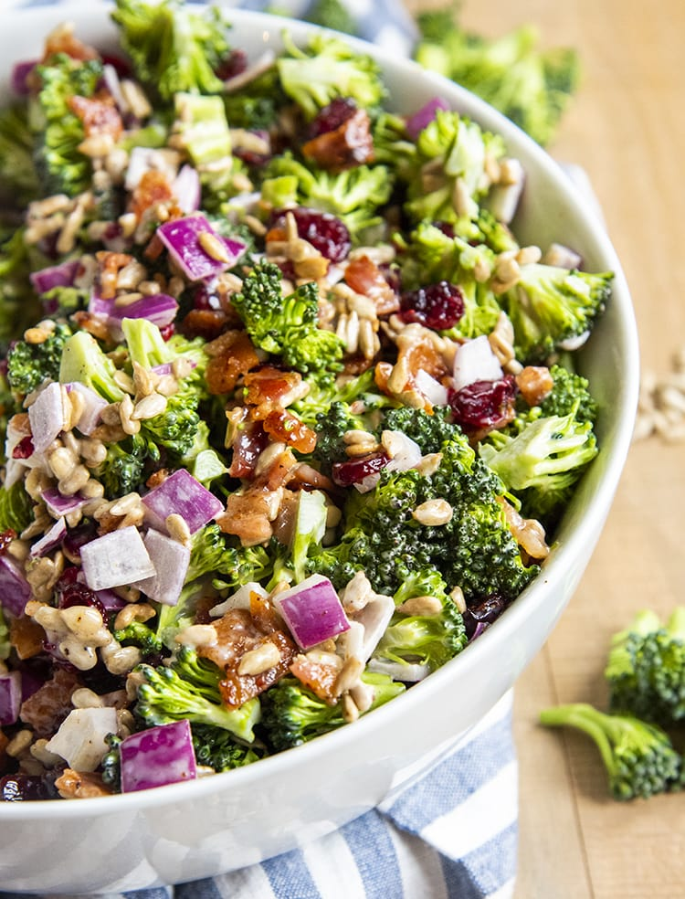 Creamy broccoli salad tossed together in a white bowl, with chopped broccoli, bacon, red onion, sunflower seeds, and dried cranberries in a creamy sauce.